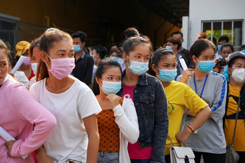 A line of women in Cambodia, all wearing face masks