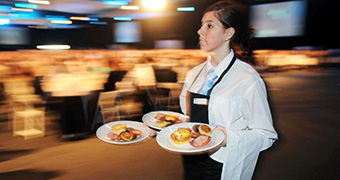 A waitress carries three dinner plates while serving food in a large room with the background blurred.