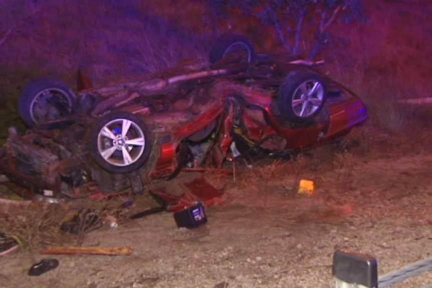 The wreckage of a red car on the side of the road after it rolled on the Kwinana Freeway.