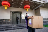 A FedEx employee removes a box from the Chinese Consulate as lanterns hang by the door.