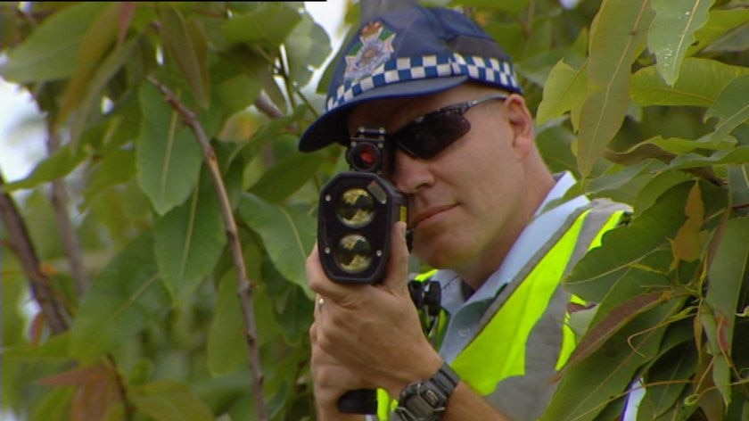 TV still of close-up of anonymous Qld police officer with a speed camera in Brisbane.