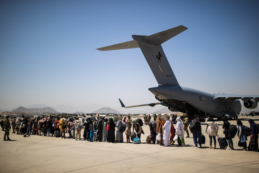 Afghan families lining up on the tarmac