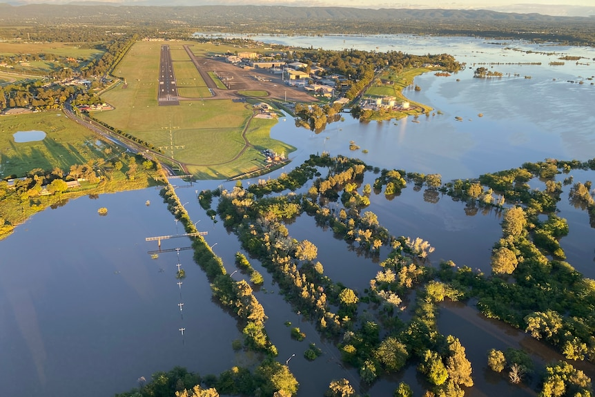 An aerial view of widespread flooding near an airstrip.