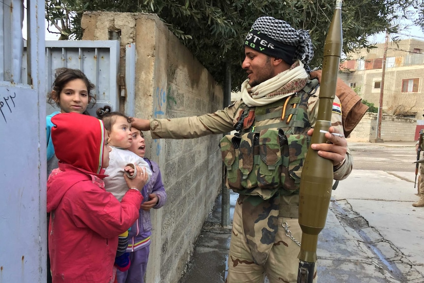 A soldier on the street holds a weapon and speaks to children recently liberated from Islamic State in Mosul, Iraq.