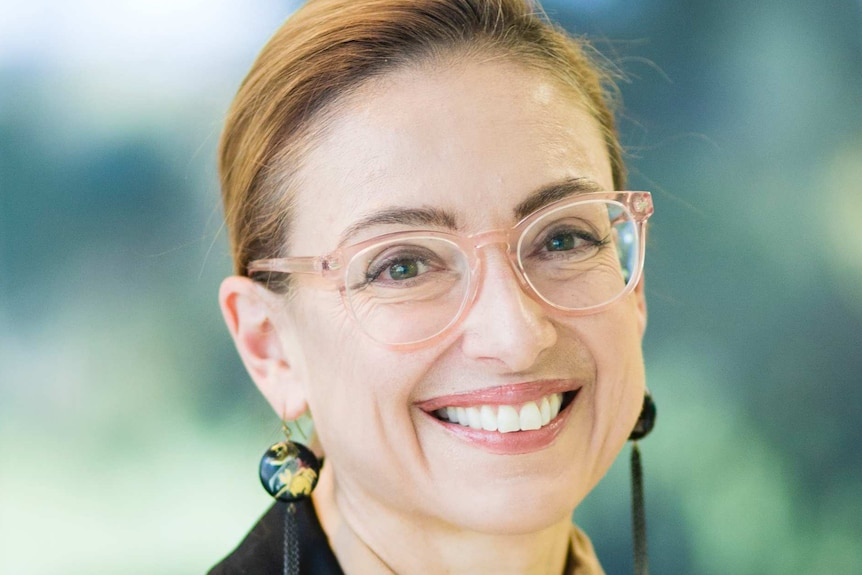 A headshot of a woman wearing glasses, blouse and a vest.