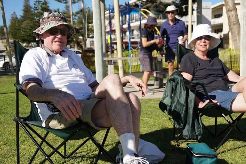 An elderly couple sit in a park enjoying the sunshine