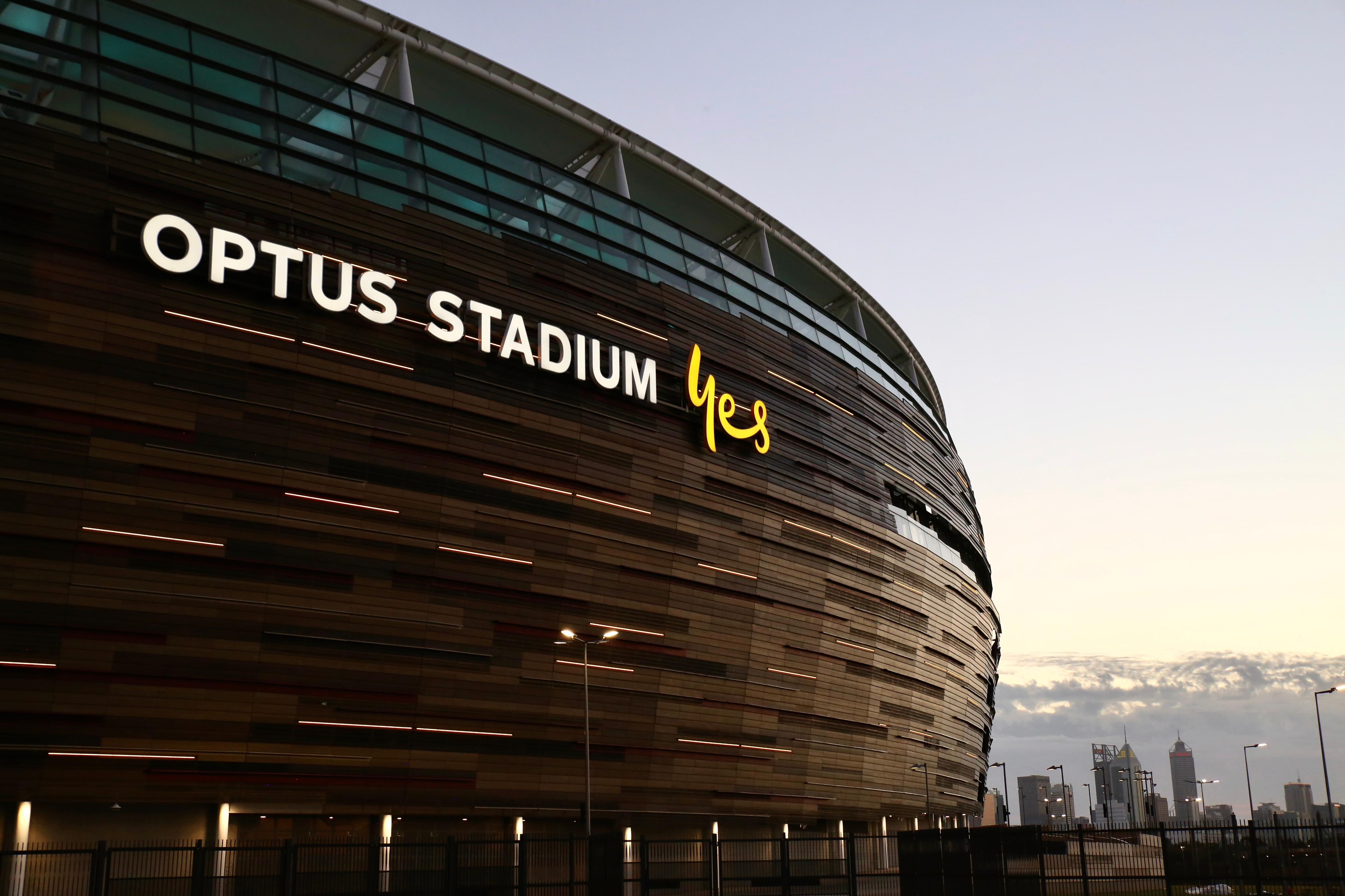 The hulking Perth stadium fills the frame with the Perth city skyline small in the bottom corner at dusk