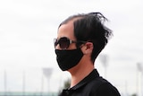 A woman in the CBD wears a face mask and sunglasses on a grey day. August 17, 2020