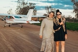 Two women stand smiling in front of a small plane on a runway.
