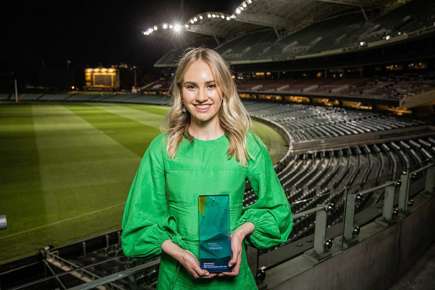 A young woman holds a trophy with a large sports stadium in the background