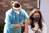 One nurse in full PPE is vaccinating a young man, while another nurse watches over them.