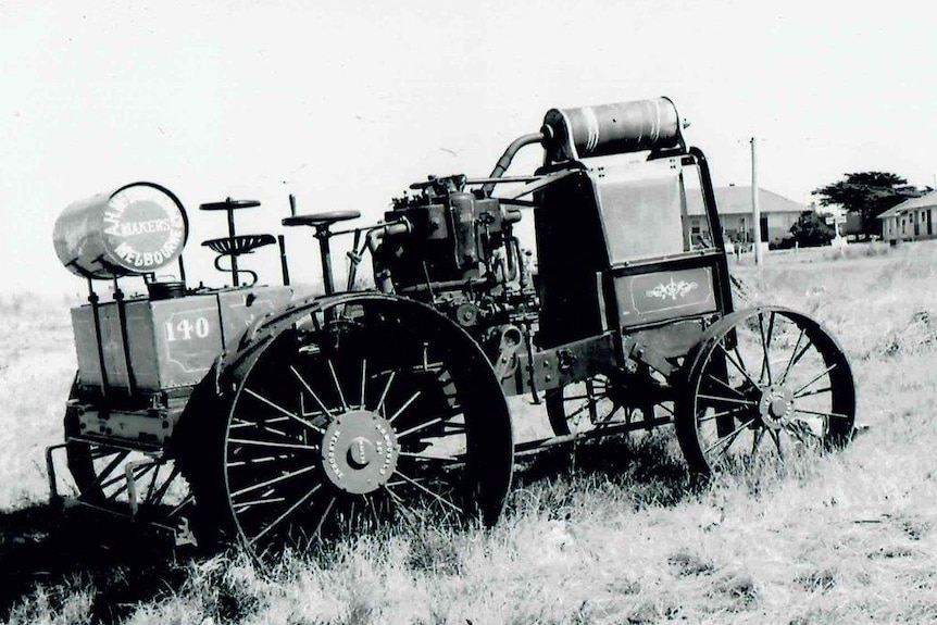 A black and white photo of an old tractor in a field.