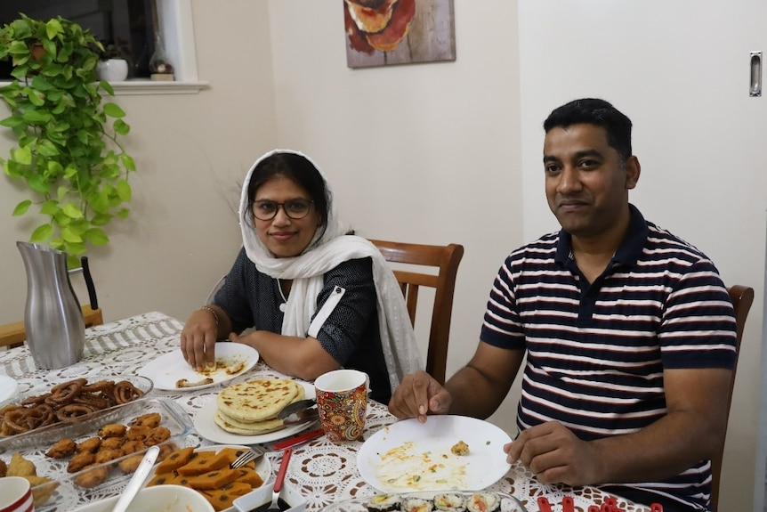 A woman and a man sitting at their dining table enjoying a meal with their family.