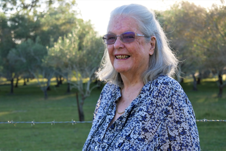 A smiling, elderly woman with grey hair stands near a barbed wire fence & olive trees. The setting sun back-lights her hair.