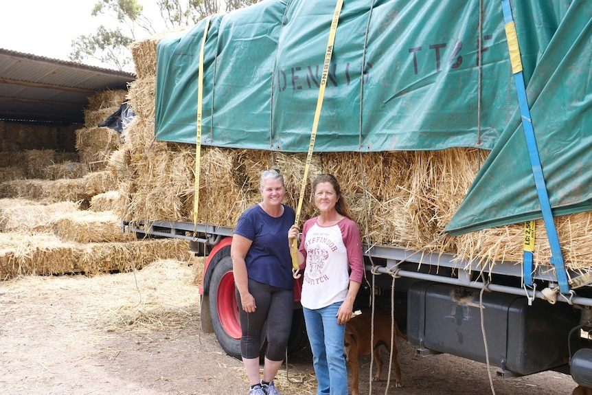 Two women stand in front of a loaded truck filled with hay.