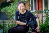 Lee Chong sits smiling at a small metal table outdoors, with her arms around her black guide dog Genie.