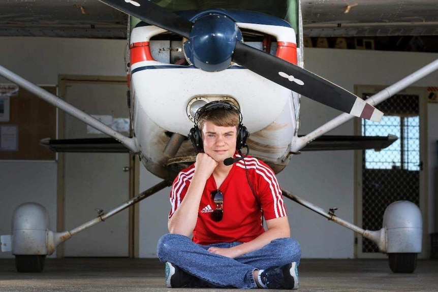 A young man sits in front of a plane.