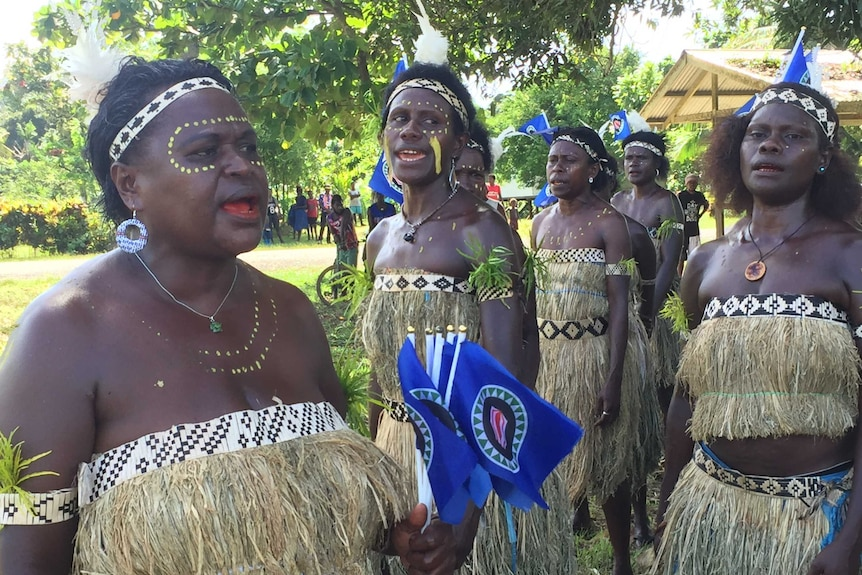 Women in tradition dress with flags and their bodies painted celebrate the opening of voting.