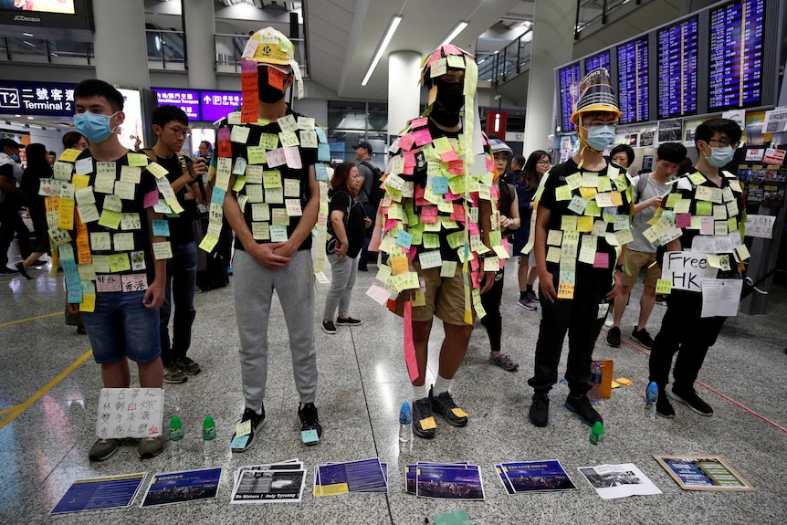 A group of young men in Hong Kong stand in a row covered in sticky notes