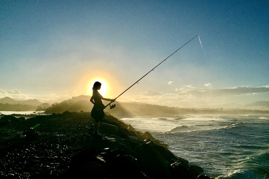 boy fishing at beach during a sunset