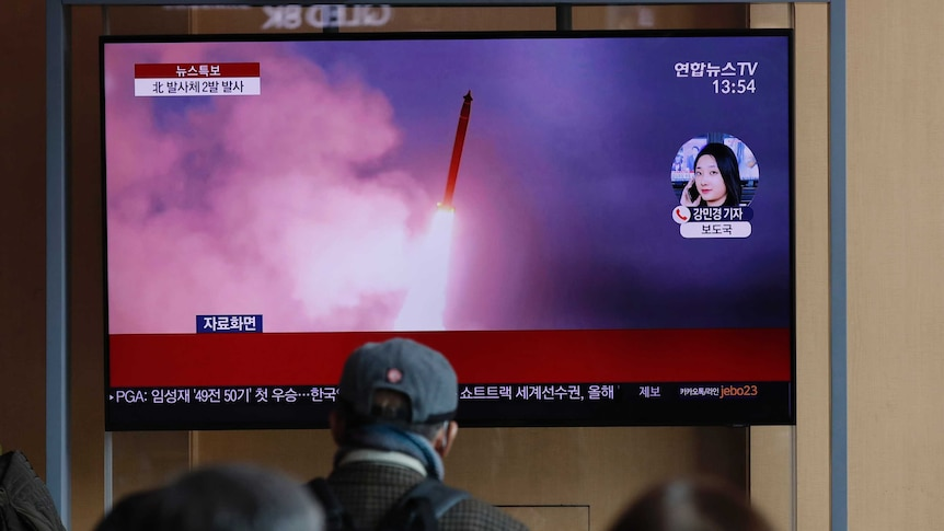 People watch a TV screen showing North Korea's firing of projectiles.