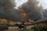 Smoke from a bushfire rises into the sky above houses in northern NSW.