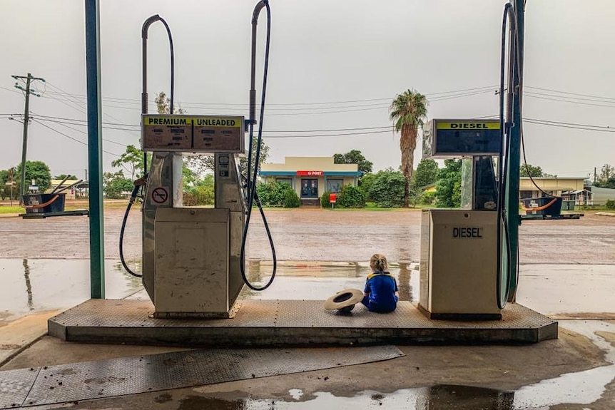 Child sits between two petrol bowsers at Windorah Service Station watching floodwaters.