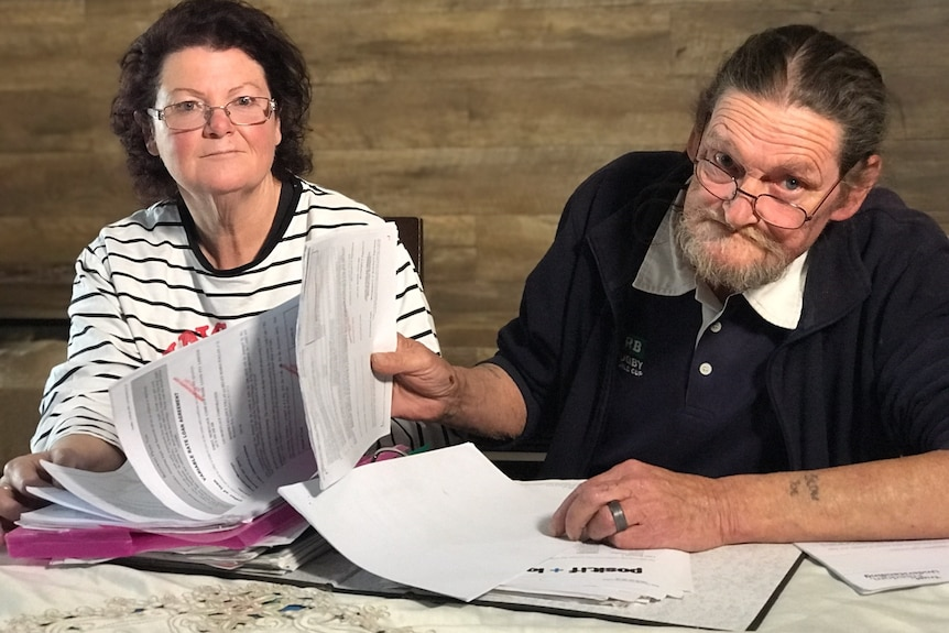 an older man and woman looking at debt documents
