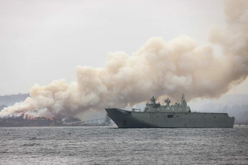 a navy ship near burning bushland