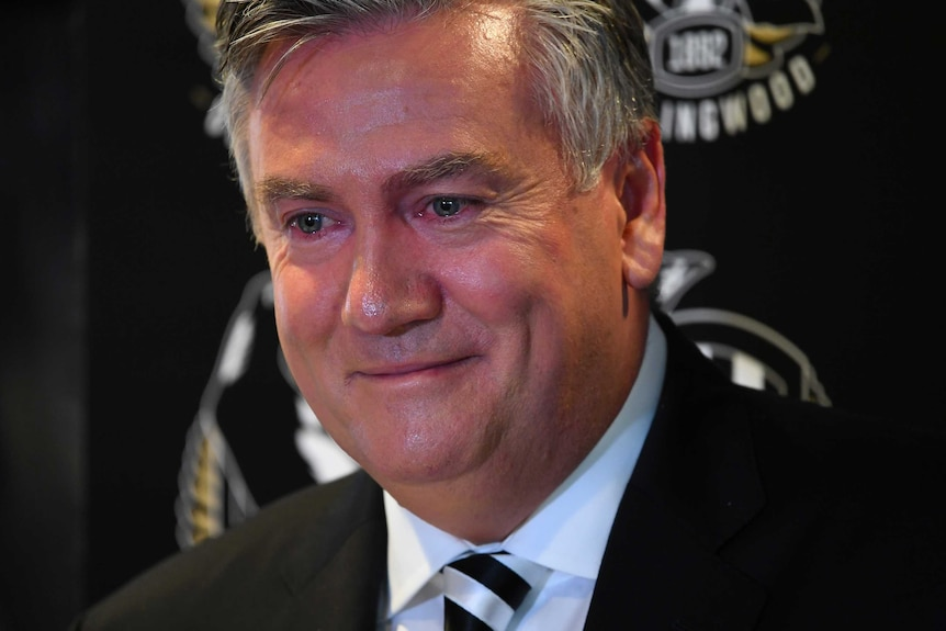 Eddie McGuire has red, teary eyes as he smirks during a press conference