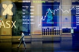Pedestrians are seen reflected on the Australian Stock Exchange trading board in Sydney