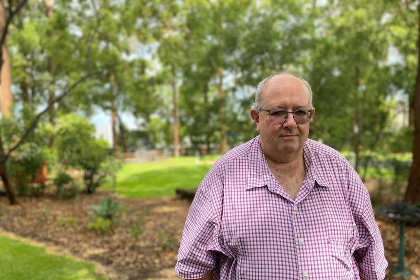 A middle-aged man in a plaid shirt walking through a park.