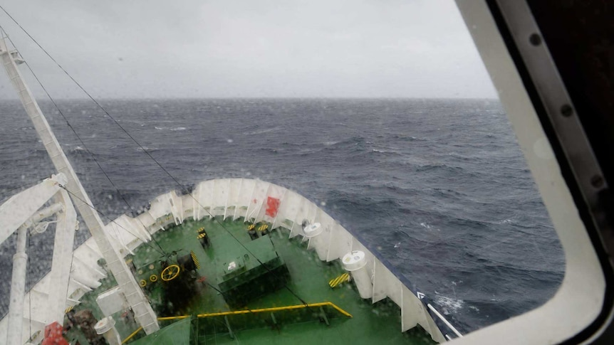 A ship in the open ocean tilts against the waves.