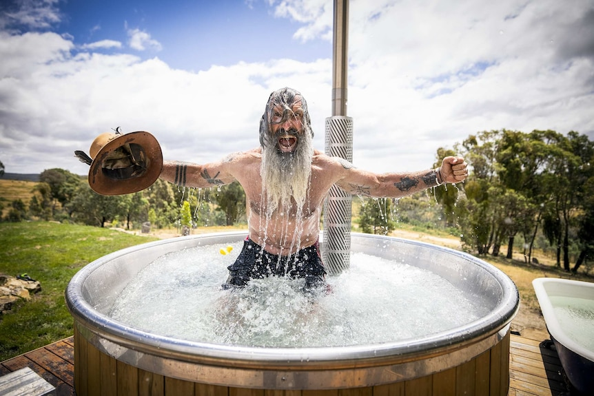 Mark takes an ice bath, holds his hat in one hand