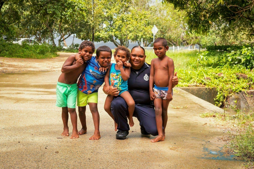 An Aboriginal police liaison officer crouching with four small children all smiling for a photo.