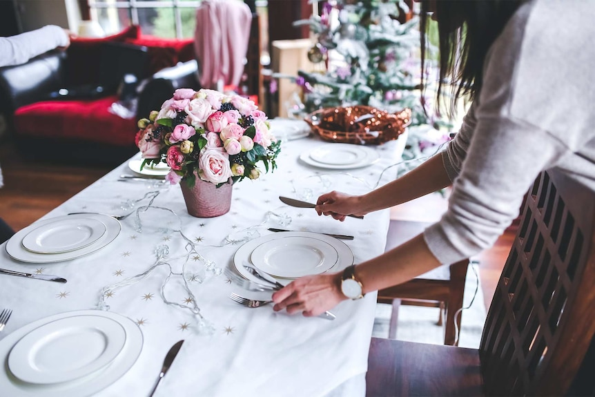 A woman setting the Christmas table to depict how to help lonely or bereaved people over Christmas.