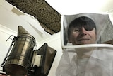 Scott Whitaker smiles at the camera with the bee hive exposed in the ceiling above him. He is holding a smoke.