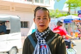 A woman in a Cambodian flag scarf stands on a street corner while cars and scooters go by