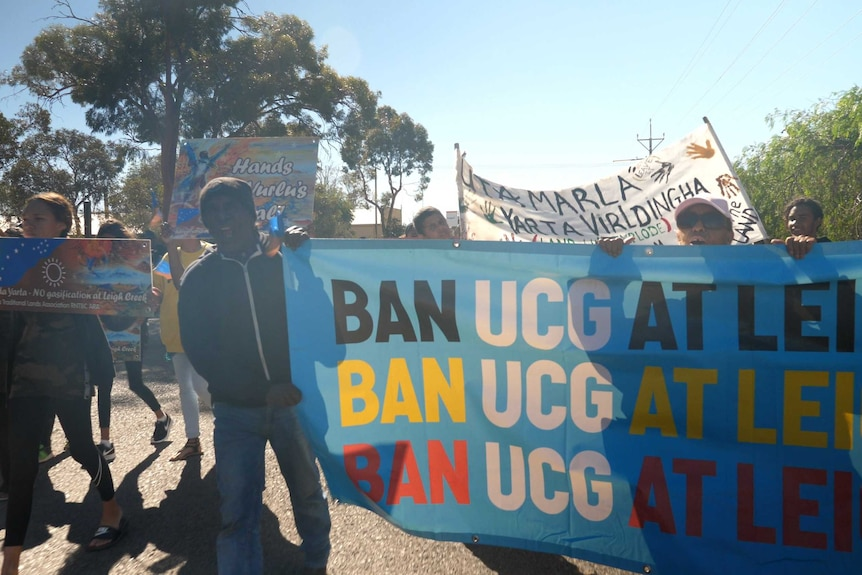 People march on a sunny day holding signs declaring a ban on underground coal gasification at Leigh Creek