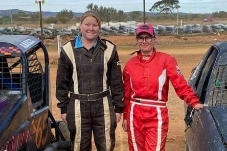 Two women in racing overals between two racecars at the dirt racing track, white bumper tyres in background