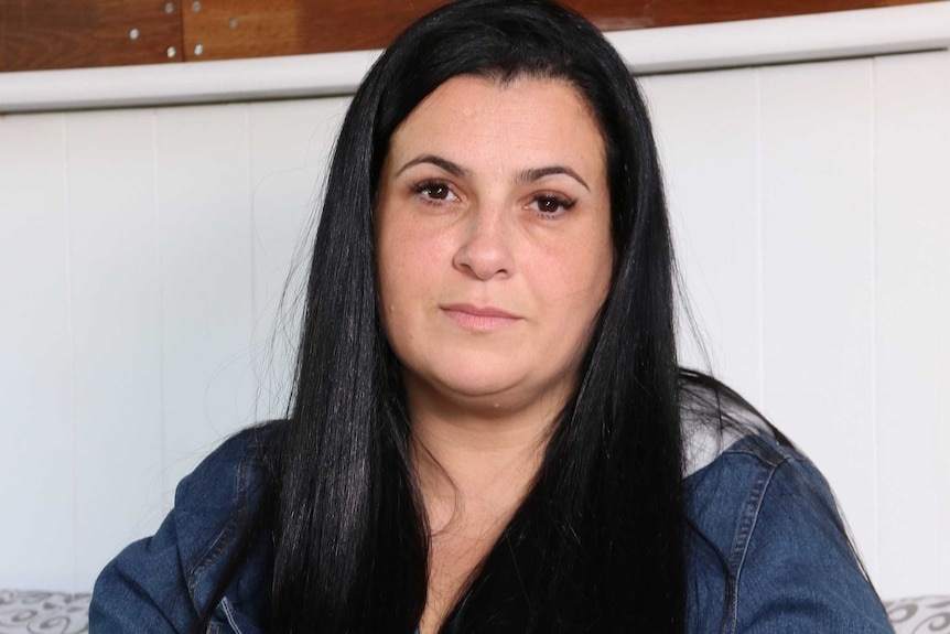 A woman with long black hair and a denim jacket sits on a couch.