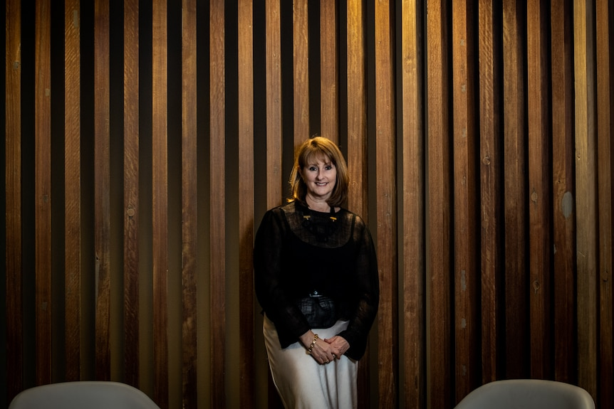 Kirsten O'Doherty stands against a wood panel background with a light overhead. She is smiling and wears a black shirt.