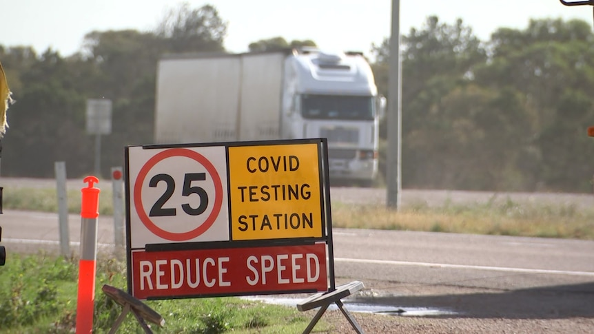 A COVID testing station sign with a truck passing in the background on the other side of the road