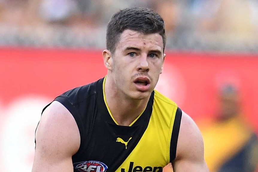 Jack Higgins moves to grip the Sherrin with two hands during an AFL game for the Richmond Tigers.