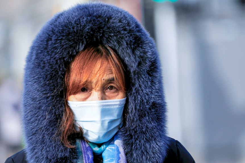 A woman in a face mask and a big hooded blue fur coat