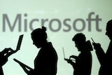 Silhouettes of laptop and mobile device users are seen next to a screen projection of Microsoft logo