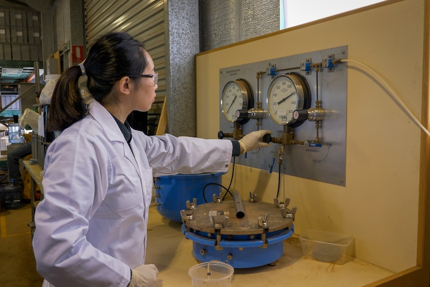 USQ PHD candidate Hanlu Zhang watches the pressure gauges while testing soil, Toowoomba, August 2021.