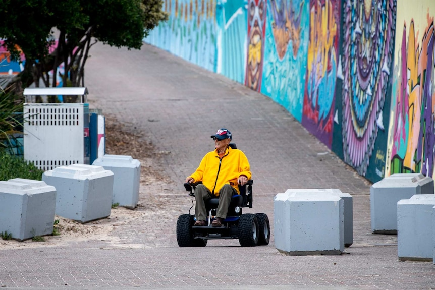 A man with a bright yellow top wheels down the street in a motorised wheelchair.