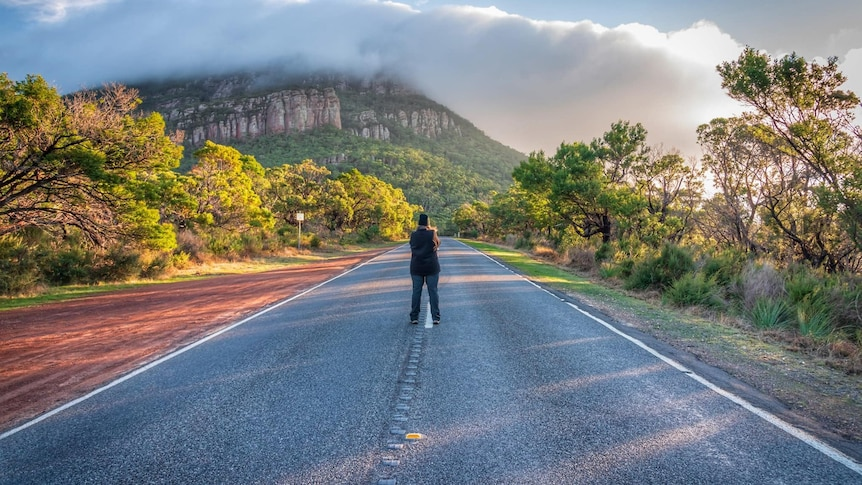 A person stands in the middle of the road in Dunkeld