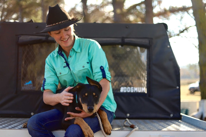 A woman with an akubra sitting in the back tray of a ute hugging her farm dog who's on her lap.